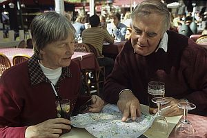 Elderly couple at an outdoor cafe looking at a map
